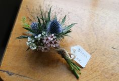 The Fabulously Wild outonniere of Champagne Grass, Thalaspi, Eryngium, Wax Flower Blossom and Gypsophilia