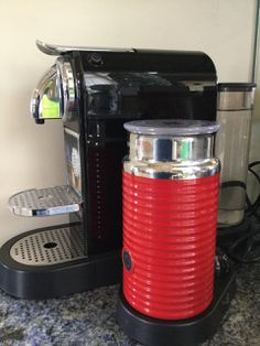 NESPRESSO D110 ESPRESSO COFFEE MAKER IN BLACK WITH CHROME ACCENTS. LOT ALSO INCLUDES A NESPRESSO MODEL 3194 AEROCCINO AUTOMATIC MILK FROTHER IN RED AND CHROME. BOTH ITEMS ARE IN LIKE NEW CONDITION.