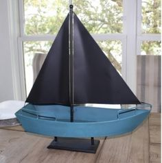 "Slightly shabby chic metal boat that resembles a Chinese Junk or Dhow. The boat and sails are made of metal and measure 20"" long and 22"" wide. The hull is a slightly distressed blue and generous enough to hold anything you can think of. Use it as a collection point for keys, phones or even condiments at your next party. Or fill it with found shells or rocks and put it on the mantle for a splash of nautical decor."