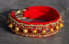 Indian inspired opulence is realized in this exceptional handmade red luxury dog collar. You will command everyone's attention when you dress your dog in this gorgeous collar. Brilliant red vintage Japanese raw silk covers a secure, heavyweight nylon webbing core. Ornate hand beading includes gold dyed freshwater pearls, gold rimmed flat red glass beads, and a variety of gold and red glass beads, each kissed with a tiny gold or red glass seed bead. $199.00