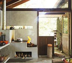 Com paredes revestidas de tecnocimento (ns Brazil), a cozinha recebe luz natural através de várias aberturas de vidro, como a bandeira junto ao telhado, o rasgo atrás do fogão a lenha e os painéis na metade superior da porta. Piso de ladrilhos hidráulicos da Casa Franceza.