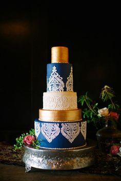 A blue and gold wedding cake with a white icing overlay. Very elegant!