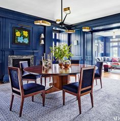 A Warhol flower painting overlooks the dining room's vintage table, which is joined by wood chairs designed by Mark Cunningham. The chandelier is by Achille Salvagni, and the sconce near the fireplace is by Jean Royère. The custom-made carpet is by the Mitchell Denburg Collection.