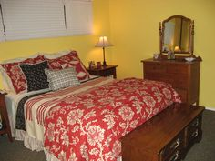 French country bedroom. I'm on the way to bringing my French country bedroom to reality!: yellow walls, red bedding (Kohls), antique dresser, white shutters, ticking stripe lampshade (Target), Lane hope chest