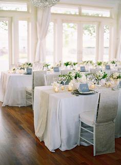 schlichte weiße Tischdeko mit weißen Blumen und kleinen Kerznehaltern