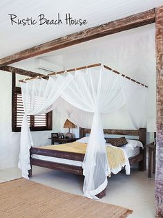 Rustic beams. Sheer curtains trimmed in opaque fabric. White stucco walls. Window in dark wood. Primitive bed.