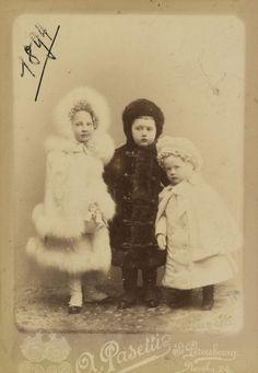Princesa Tatiana Constantinovna, Príncipe Constantino Constantinovich e Príncipe Oleg Constantinovich. Eles estão de pé em uma fila com Princesa Tatiana para a esquerda e Príncipe Oleg para a direita. Eles estão usando roupas de inverno. A fotografia é datado '1894' no canto superior esquerdo.
