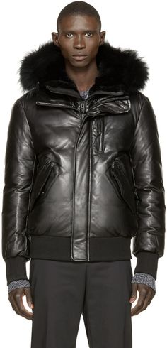 Leather down jacket in black. Stand collar and hood with rabbit fur lining and raccoon fur trim. Zipper closure at front. Layered second stand collar and zipper closure with press-stud placket. Zippered pocket at chest. Zippered and patch pockets at waist. Ribbed cuffs and hem. Leather logo patch at hood in tan. Tonal stitching.