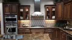 PebbleCreek Design Center: European Beach cabinets in Walnut stain. GE Monogram appliances. Granite-Carmel Fantastico. Custom order & design backsplash, Cream Marfil and smoked glass by AZT.