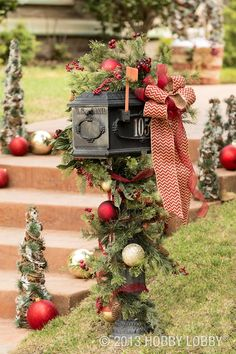 Increase your home's Christmas curb appeal by decorating your mailbox with ornaments, greenery and bows.