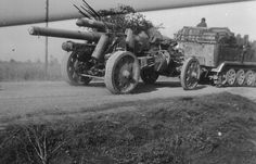 """533  German 10cm  being towed by SD-Kfz-7  Halftrack.  The Sd.Kfz. 7 was a half-track military vehicle used by the German Wehrmacht, Luftwaffe and Waffen-SS during the Second World War. (Sd.Kfz. is an abbreviation of the German word Sonderkraftfahrzeug, """"special purpose vehicle"""". A longer designation is Sd.Kfz. 7 mittlerer Zugkraftwagen 8t, """"medium towing motor vehicle 8t""""."""