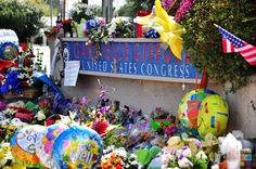 "A view of the grassroots tribute memorial which grew up at Congresswoman Gabrielle Giffords' office after she and 18 other people were shot at her ""Congress on Your Corner"" event on January 8, 2011 in Tucson, Arizona. Six people lost their lives in the shooting that day."