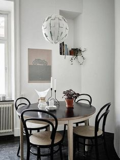 Dining space with round table and Thonet chairs in a calm Swedish home in neutrals (and a fab fireplace). Stadshem.