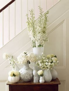 Floral arrangement: White delphinium and other white blooms arranged in a collection of milk glass.