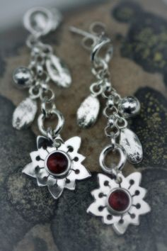 Earrings | Paarma Design  Evergreen Saxifrage  Flower of rocky slopes with sheltering lingonberries (foxberries) and a garnet heart  138 e Evergreen, Finland, Garnet, Drop Earrings, Heart, Flowers, Jewelry, Design, Jewerly