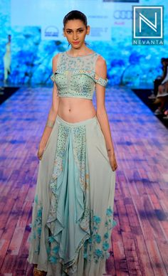 A model in an ice-blue ruffled #skirt and a contrasting crop-top by 'Rachna Sansad college of fashion design'