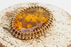 Large, vintage Topaz cabochon worked with size 15º Czech Charlotte and Miyuki seed beads in Hubble stitch.