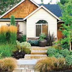 Rusty-hued Carex testacea softens the front path, while green kniphofia, plum Heuchera 'Obsidian', Libertia peregrinans 'Bronze Sword', and euphorbia surround the 'Karl Foerster' gras Low Water Landscaping, Front Yard Landscaping, Landscaping Ideas, Colorado Landscaping, Inexpensive Landscaping, Hillside Landscaping, Luxury Landscaping, Landscaping Plants, Front Gardens