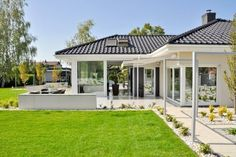 Simple, green lawn at the side of this small, modern, single story home. By: Abakon sp. z o.o. spółka komandytowa