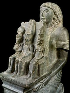 Statue of Ramesses-Nakht holding the Theban Triad. Ramesses-Nakht (the High Priest of Amun at Thebes from the reigns of Ramesses IV until that of Ramesses IX,20th Dynasty) donating a statue of the Theban family,Amun in the god seated in the middle of the little group wearing tall feathers on his flat topped crown,to his left his wife the goddess Mut with a special tall crown and their son Khonsu sitting at his father's right. •Egyptian Museum,Cairo•