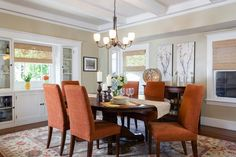 Beautiful orange chairs bring color to the traditional dining room