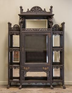 "Ebonized Victorian Aesthetic Cabinet. 19th cent. Beveled glass; carved griffins & fretwork.   Ht. 71"" W 48"" D 13"""