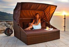 Ein großes und kuscheliges Outdoor-Bett aus hochwertigem Kunststoffgeflecht, ideal zum Herumlümmeln unter blauem Himmel. Das Dach lässt sich je nach Sonnenstand beliebig arretieren, um jederzeit im Schatten sitzen zu können.