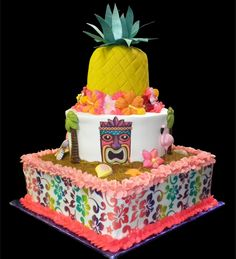 Hawaiian Birthday Cake,  White and yellow buttercream iced,   3 tiers decorated with tiki mask, palm trees, flamingos, seashells and starfish.  Wrapped with an edible floral print and topped with a whole pineapple complete with a Hawaiian flower lei. Everything on this cake is EDIBLE.  (Serves 78-135 party slices)