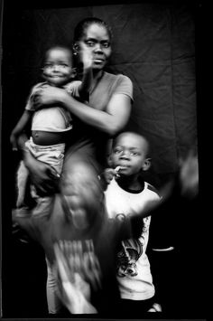 Haitian Marie Mirlande Caceus poses for a portrait with her sons, Miguel and Lilliam, and a family friend, 3-year-old Ryan, Tijuana, US-Mexico border portrait series by ph. Rodrigo Abd