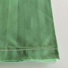 Tovagliolo in cotone con cucitura in tono colore verde acqua.