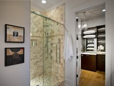 Clad in neutral-hued stones, the master bathroom shower at HGTV Smart Home 2014 is equipped with a rain showerhead and a sliding-glass door with chrome hardware. The bathroom transitions into a walk-in closet, which boasts ample storage space for clothing and bed linens.