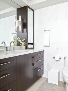 Design challenges for this bath included incorporating a lots of storage in a relatively small bathroom, removing a drop-ceiling and integrating good lighting without the  benefit of a natural light source.