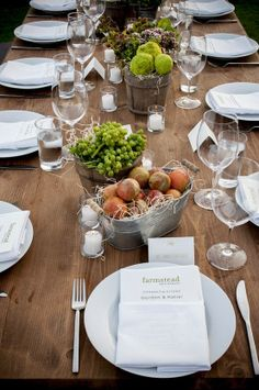 Very simple. Plain white plates and napkins, plain clear glasses and votives on a plank table. Some buckets of fruit or greens.