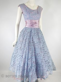 A 1950s party dress in light blue floral lace highlighted with pink stitching, over a pink lining, which gives an overall effect of lavender or periwinkle. Atta