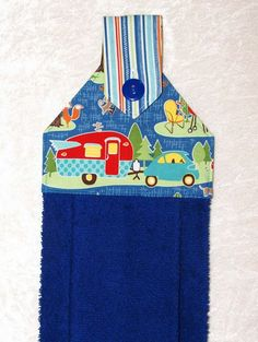 A blue hand towel with a cheerful travel trailer, car and stripes. The plush blue towel is more luxurious than a standard kitchen towel. Featuring a designer fabric with a car and travel trailer on blue and charming blue striped fabric, it is sure to add fun to your home or camper kitchen and bath.  This handmade hanging towel works well buttoned over the handle of stove, dishwasher, drawer pull, or even a knob, door knob or vertical handle with optional hanging ring. It can even be used…