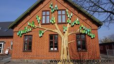 """HAPPY CITY BIRDS MURAL V.2  Hvalsø, 2015. Thomas Dambo. Made during a workshop outside a library in the town, Hvalsø outside of Copenhagen. Local kids each painted one of the 60 pre-made birdhouses, which were then hung on the """"tree"""" made on the building's facade. Everything was made from recycled materials."""