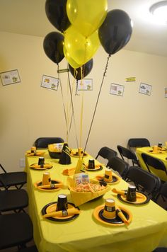 """spare room - converted to the """"party room""""  decorated with yellow & black, kids place settings, wall decorated with print outs on """"wheels on the bus"""" song lyrics with pictures"""