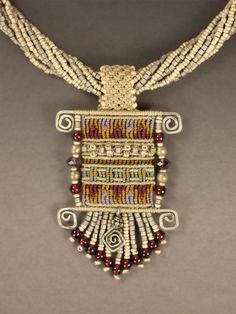 Magic Carpet  by Joan Babcock  Cavandoli knotted pendant in gray tones with burgundy, gold, orchid and blue accents.  Silver wire accents and silvery/gray seed bead multi-strand collar.