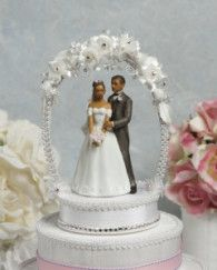or HeadbandThis cake topper features an African American couple under a delicate arch of flowers that are crystal studded. The base is made of moire and trimmed in silk cording and Czech crystals.This Item is out of Stock!