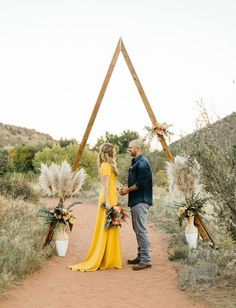 33 Boho Wedding Arches, Altars And Backdrops To Rock: triangle altar with flowers and pampas grass