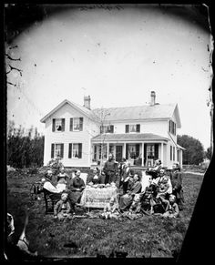 """Norwegian family posing with their household possessions, in front of their home. The man dressed in military uniform is a Civil War veteran. Madison, Wisconsin (area). Ca. 1870-1879. The family is in a yard around a table adorned with a lace cloth. Coffee cups, figurines and books are on the table. On the left is a man holding a newspaper that says """"Norden."""" A baby sits in a buggy behind him. In the rear is a man dressed in a military uniform. #Victorian #vintage #portraits #family"""
