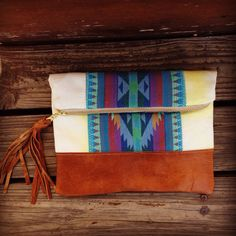 Tribal print clutch, with turquoise Aztec pattern and genuine lambskin leather base and tassel. Measures 9 inches by 10 inches wide. The lining is