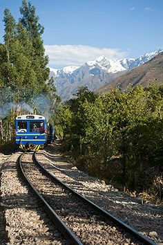 Ollantaytambo, Peru Rail train in Urumamba valley, snow covered Andes peaks in background