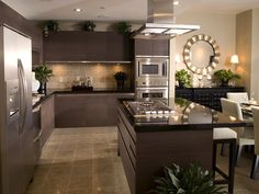 Dark kitchen design with dark cabinets, backsplash, counter tops. Island divides open layout from dining area