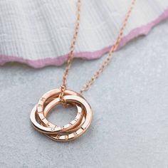A beautiful 18ct rose gold plated Russian ring necklace which is handmade in our Brighton workshop. This is a variation of our popular Personalised Interlinking Necklace with the text running horizontally along the rings, allowing for more text on each face of the ring. Our most popular personalisations include; names and dates of birth of children, names of newlyweds and the date of their special day, or any other personal sentiments that are special to you or the recipient of this lovely…