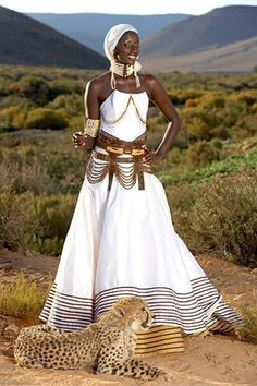 Occasion: This woman is wearing a traditional South African wedding dress. The well-known white dress is worn but is also detailed with African jewelry. The unique accents such as the head wrap and neck collar symbolize tradition and African culture