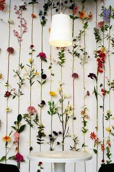 flowers taped to white wall wedding backdrop