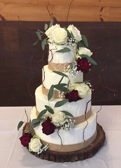 "Simple, rustic buttercream wedding cake with burlap ribbon. Accented with curly ""twigs"", red and white roses, and eucalyptus."