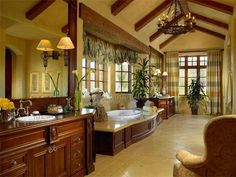 In the master bathroom, vaulted ceilings and exposed beams add to the rich European feel, while a grand chandelier, dark woods and hand-laid tile floors complete the romantic and sophisticated design.
