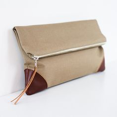 "Clutch in olive.  Canvas fabric, lined w/ cream cotton. Small interior pocket w/ faux leather zipper pull & corners. Measures 10.5"" x 5.5"" (when folded over) or 9"" (when open)."